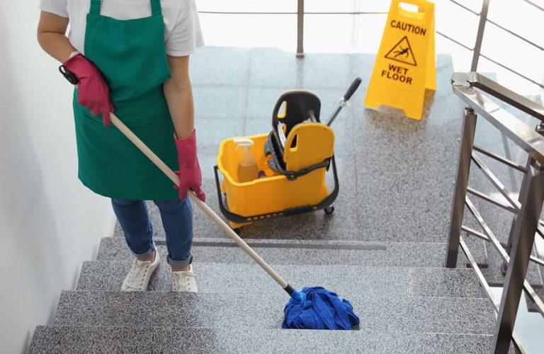 a janitor mopping a staircase of a building